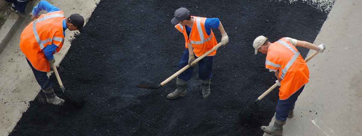 Workers Spreading Fresh Asphalt