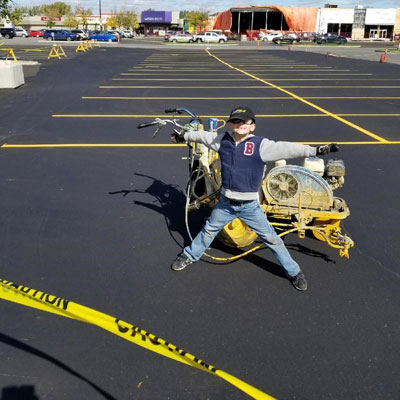 Fresh slurry seal and line marking at the Mall at Lawson Heights Mall with our youngest employee